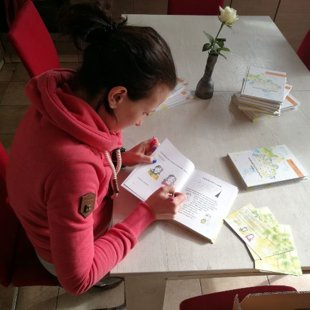 Kristīne paraksta grāmatiņu